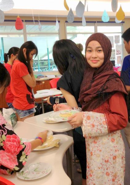 Uczennica z Malezji degustuje pierogi w dniu międzynarodowym