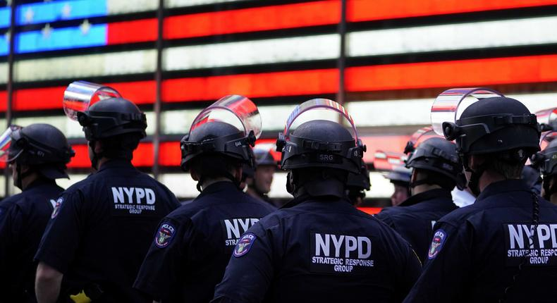 NYPD police officers watch demonstrators in Times Square on June 1, 2020, during a Black Lives Matter protest. - New York's mayor Bill de Blasio today declared a city curfew from 11:00 pm to 5:00 am, as sometimes violent anti-racism protests roil communities nationwide. Saying that we support peaceful protest, De Blasio tweeted he had made the decision in consultation with the state's governor Andrew Cuomo, following the lead of many large US cities that instituted curfews in a bid to clamp down on violence and looting