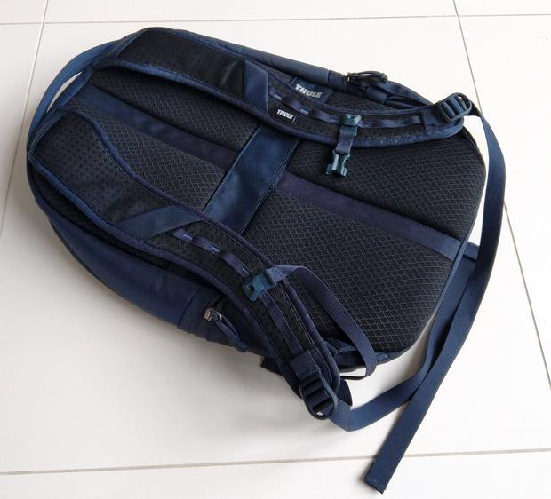Z tyłu plecaka widoczny jest poprzeczny pas do mocowania plecaka na rączce walizki