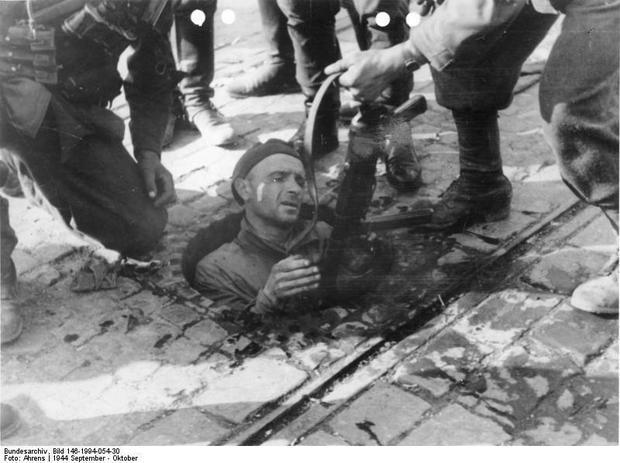 Powstaniec warszawski wychodzi z kanałów na terenie zajętym przez Niemców