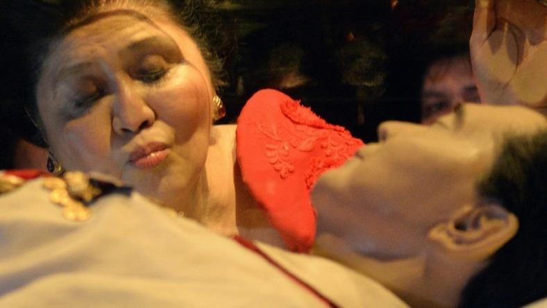 This file photo taken on July 2, 2014 shows former Philippine first lady Imelda Marcos kissing the glass case bearing her late husband and former president Ferdinand Marcos
