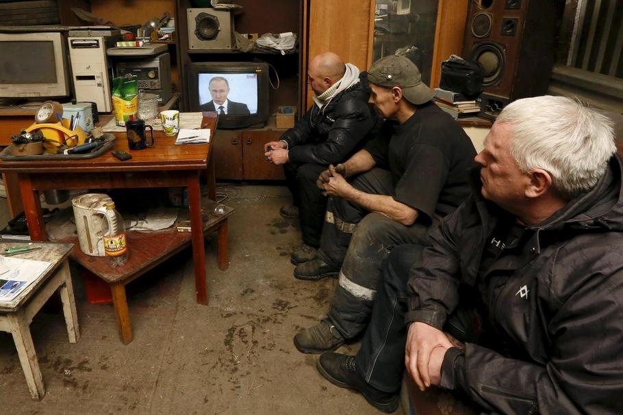 Workers watch a TV broadcast of Russian President Putin address to the Federal Assembly at an auto r