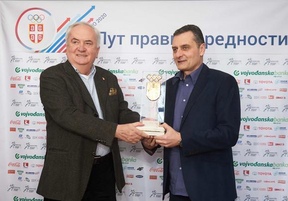 Božidar Maljković, predsednik Olimpijskog komiteta Srbije, uručuje trofej Zoranu Terziću