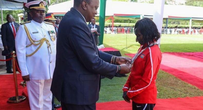 President Uhuru Kenyatta awards decorated athlete Mary Keitany with the OGW title at State House on December 12, 2019