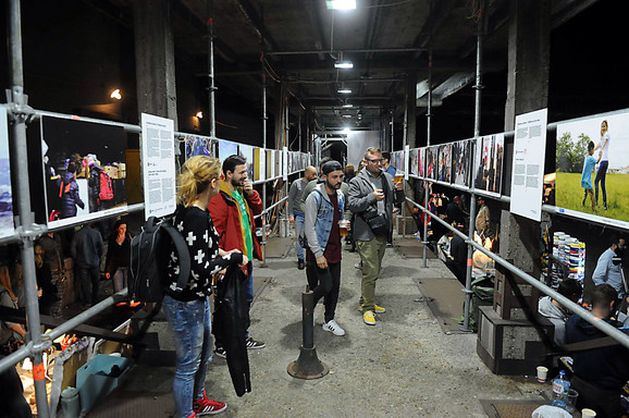 Prisutni razgledaju izložbene fotografije posvećene migrantima