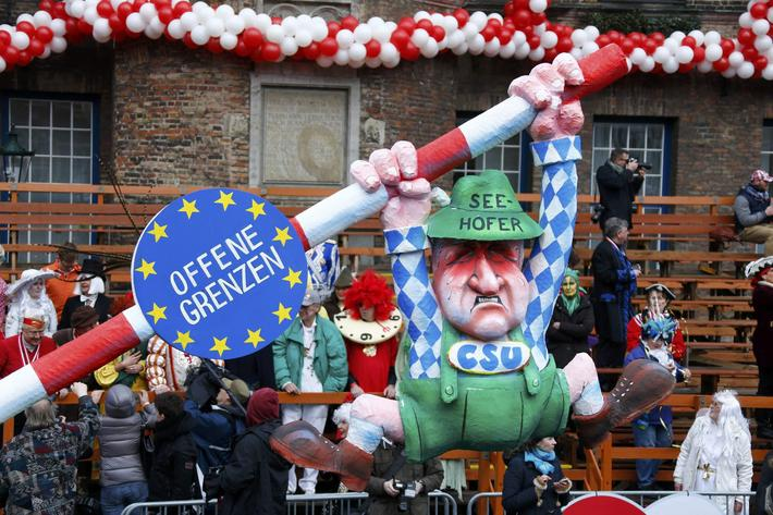 Carnival revellers wave from a window despite Rosenmontag parade being cancelled in Duesseldorf