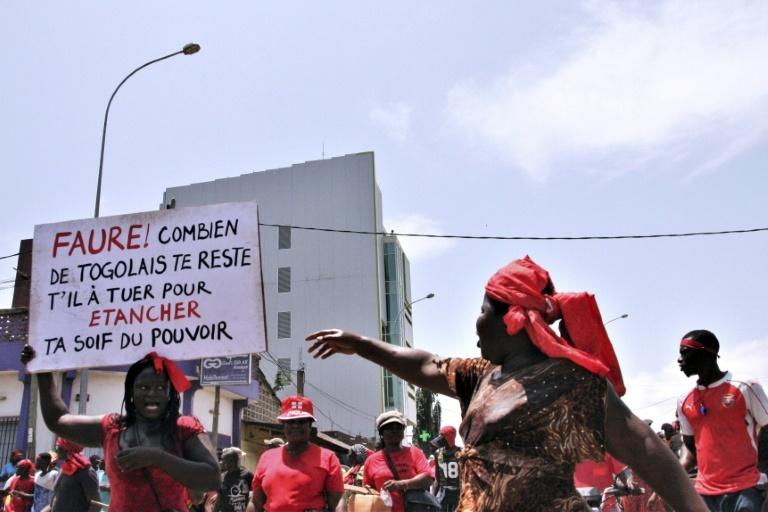 "October 2017: A woman at a protest rally in Lome holds up a placard reading ""Faure ! How many Togolese do you still have to kill to quench your thirst for power?"""