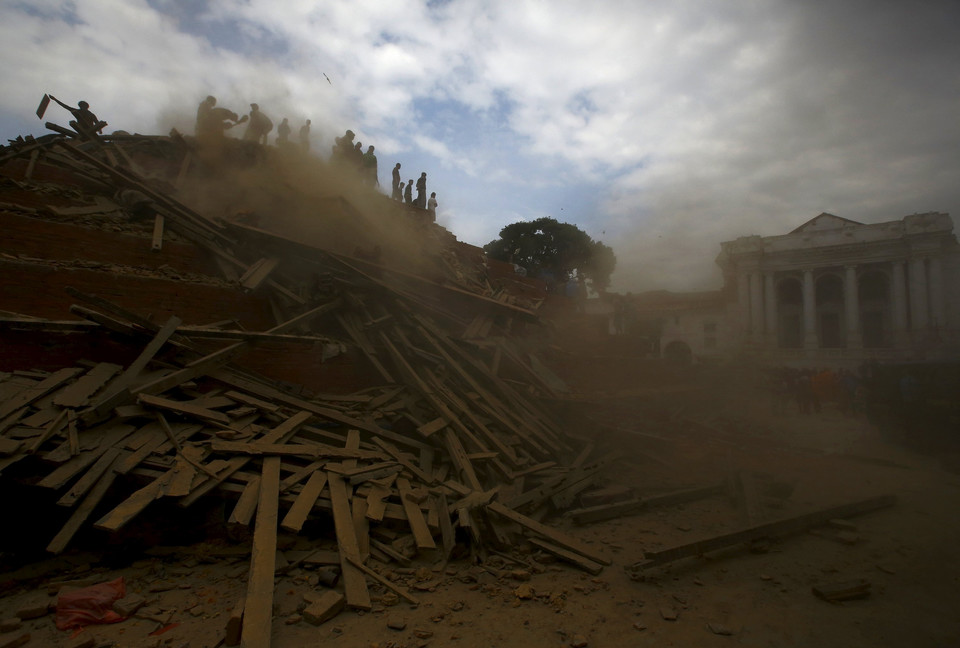 People work to rescue trapped people inside a temple in Bashantapur Durbar Square after an earthquake hit, in Kathmandu