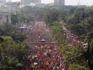 A Philippine flag flutters as devotees parade the black statue of Jesus Christ during the annual Bla