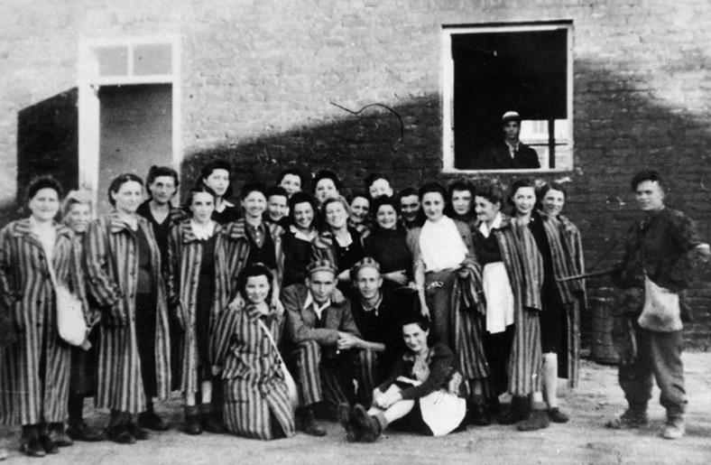 """Grupa żydów z Gęsiowki uwolnionych przez żołnierzy kompanni """"Giewont"""" Batalionu """"Zośka"""" 5 sierpnia 1944 roku. Zdjęcie na terenie obozu. Po prawej stronie, na ziemi siedzi Renata Preczep (potem Lubińska), która przeżyła Powstanie. Więzień obok niej (w czarnej marynarce) nazywa się Bronisław Miodowski (potem Bernard Miodon z Paryża). Wśród więźniarek rozpoznano także: Hankę Lux (mieszka w Australii) i Marię Morecką"""