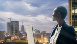 Businesswoman holding her laptop by the Nairobi city skyline