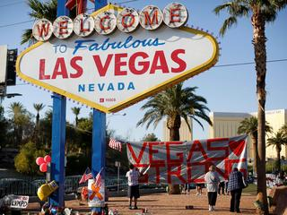 "People sign a banner near the ""Welcome to Fabulous Las Vegas"" sign following the Route 91 music fest"
