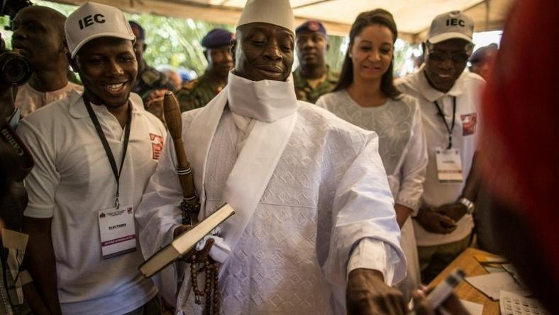 Incumbent Gambian president Yahya Jammeh (C) has his finger inked before casting his marble in a polling station in a presidential poll, in Banjul on December 01, 2016