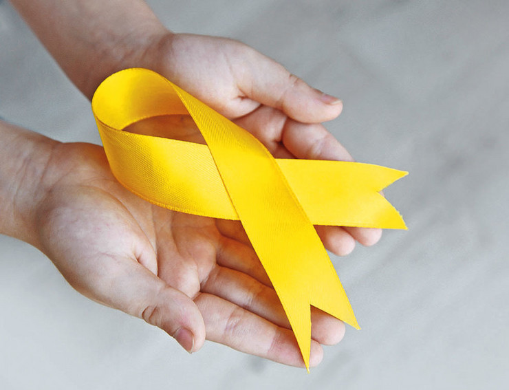 stock-photo-baby-hand-holding-yellow-ribbon-on-color-background-484127545