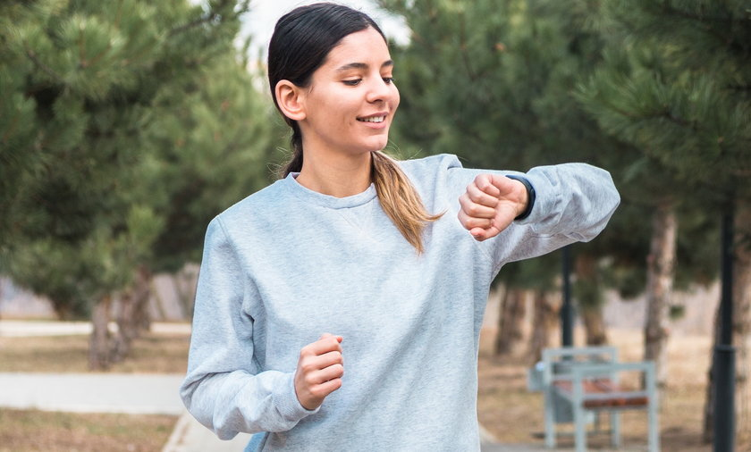 cheerful woman checking her smartband after morning run in park. girl checking burned calories after