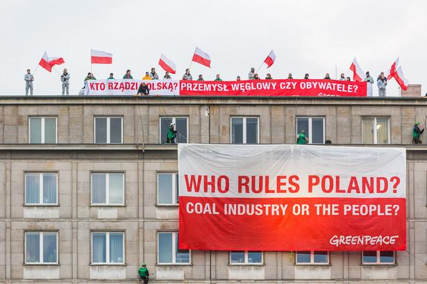 """Fot. Greenpeace. Aktywiści wspięli się na budynek Ministerstwa Gospodarki i wywiesili transparent z hasłem """"Kto rządzi Polską?"""""""
