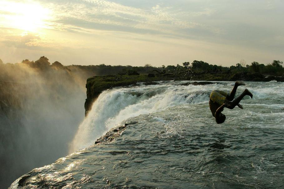 A Zambian man somersaults into a pool at the edge of the 110 metre high main falls of the Victoria F