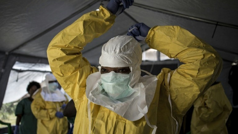 A medical worker puts on protective gear as she prepares to enter an ebola treatment centre run by The Alliance for International Medical Action (ALIMA) in Beni, in the Democratic Republic of Congo