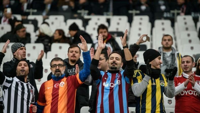 Besiktas, Fenerbahce, Galatasaray and Trabzon's supporters cheer prior to the Ziraat Turkish Cup football match between Besiktas and Kayserispor on December 14, 2016 at Vodafone arena stadium, in Istanbul