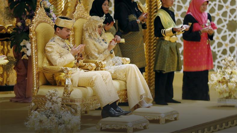 Brunei's newly wed royal couple, Prince Abdul Malik and Dayangku Raabi'atul 'Adawiyyah Pengiran Haji Bolkiah, pray during the enthronement ceremony at their wedding in the Nurul Iman Palace in Bandar Seri Begawan