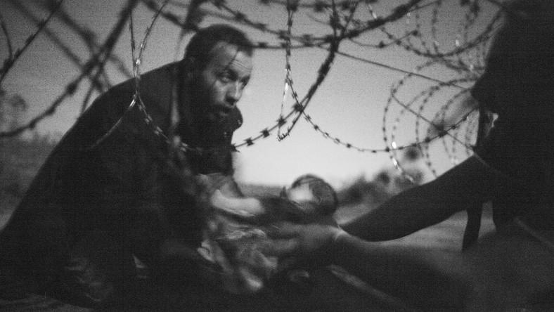 Zdjęcie Warrena Richardsona pokazujące uchodźcę podającego dziecko przez płot na granicy między Serbią a Węgrami. Ta fotografia okazała się prasowym zdjęciem roku 59. edycji konkursu World Press Photo