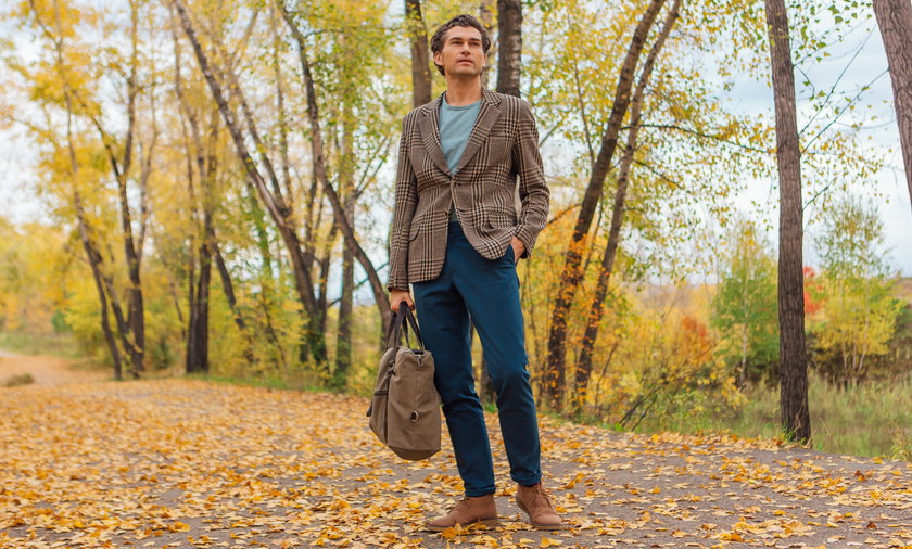 Tall handsome man with a bag on the autumn alley