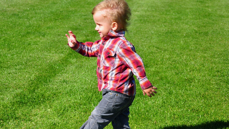 Dziecko maszeruje po trawie