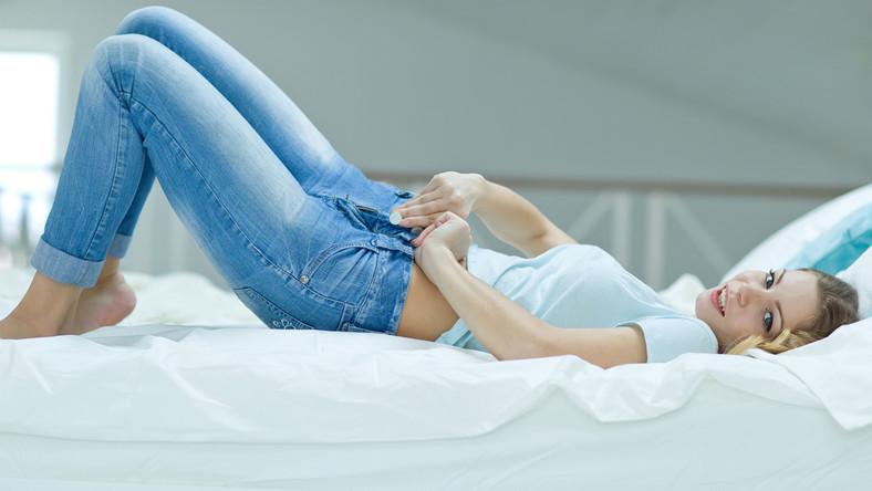 Kobieta na łóżku zakładająca dżinsy