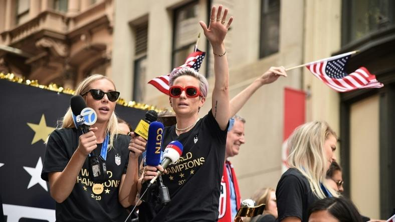 World Cup star Megan Rapinoe waves a US flag as the US women's World Cup-winning soccer team is feted with a ticker tape parade in New York