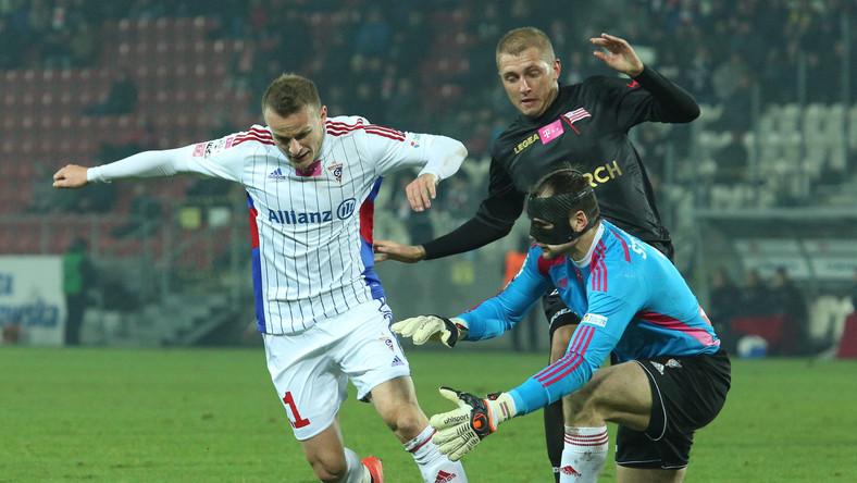 Zawodnik Górnika Zabrze Roman Gergel (L) wspiera swojego bramkarza Pavelsa Steinborsa (P) którego atakuje Deniss Rakels (C) z Cracovii