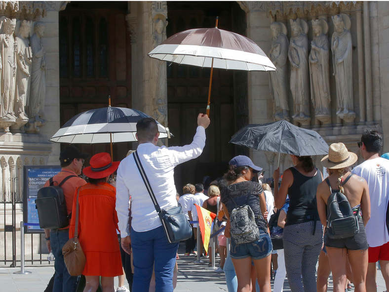 A Spanish tourist group shelter from the sun under umbrellas as they visit the Notre Dame cathedral in Paris, France, on August 6, 2018. Three French cities have banned the most polluting cars from the roads because of pollution linked to the current heat wave in Europe.