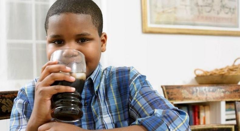 Young boy drinking soda