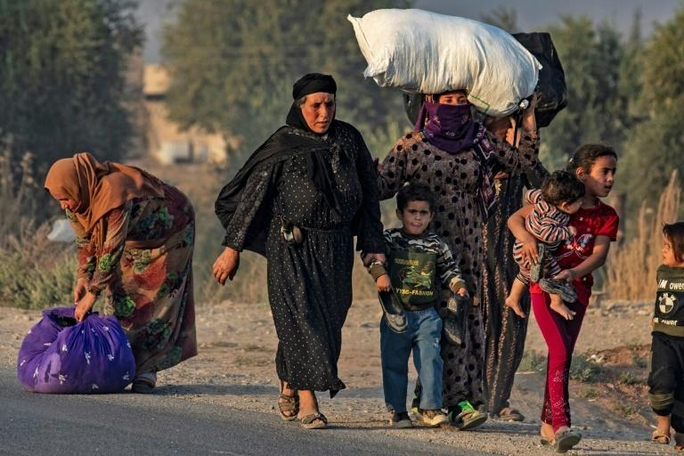 Civilians flee amid Turkish bombardment on Syria's northeastern town of Ras al-Ain in the Hasakeh province along the Turkish border on Wednesday
