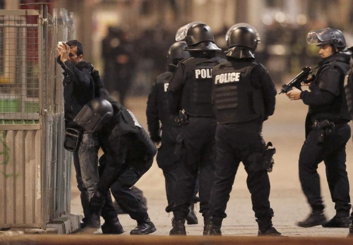 French spolice stop and search a local resident during an operation to catch Paris attack fugitives