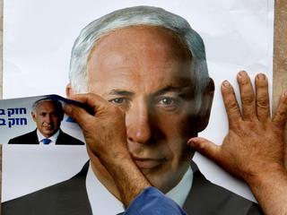 FILE PHOTO: A Likud party supporter puts up a poster depicting party leader Benjamin Netanyahu in th