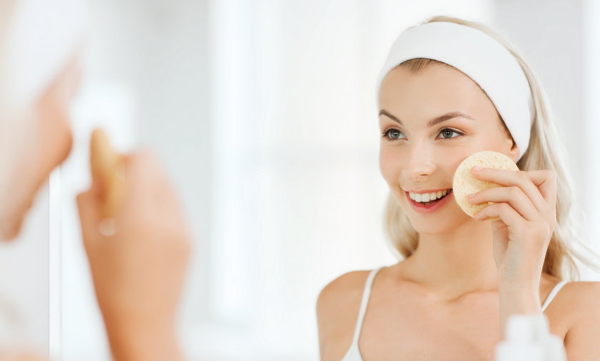 young woman washing face with sponge at bathroom