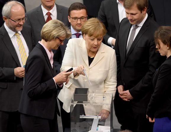 Merkelova ubacuje svoj glasački listić u kutiju