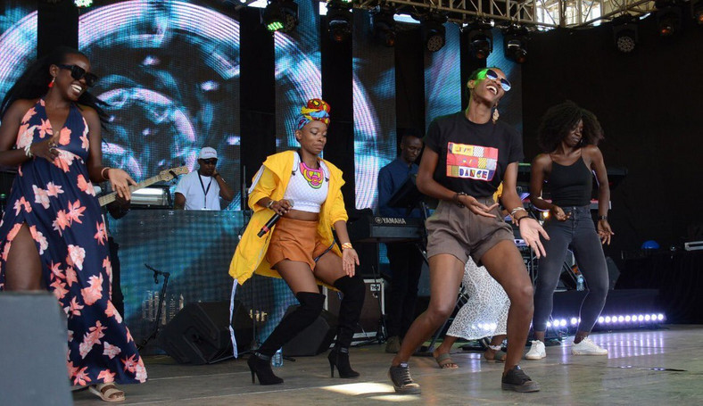 Phy dancing on stage with some female fans at the Koroga Festival (Image by Capital FM Kenya)