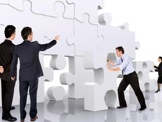 business teamwork - business men making a puzzle