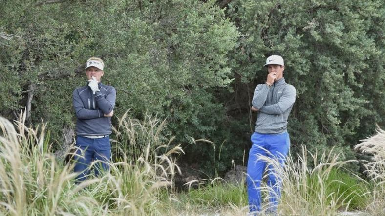 Thorbjorn Olesen (R) and teammate Soren Kjeldsen of Denmark contemplate a way of hitting out of the bushes on the third day of the Golf World Cup in Melbourne on November 26, 2016