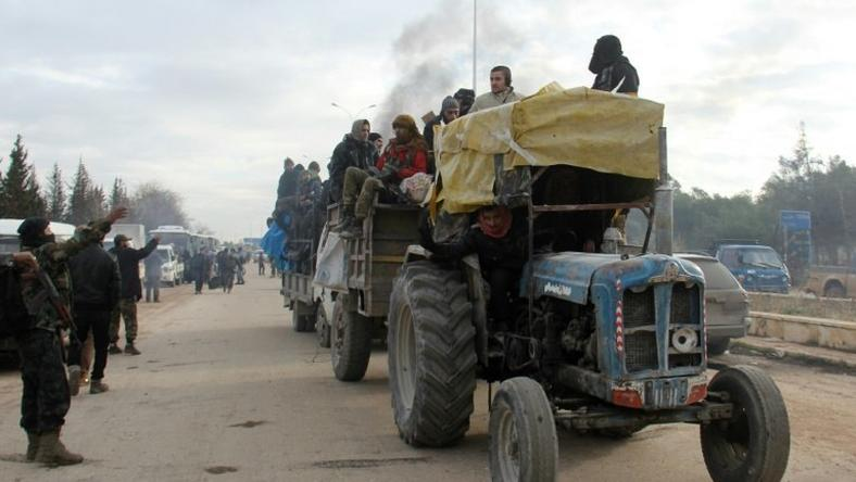 A tractor carrying people evacuated from rebel-held neighbourhoods of Aleppo arrives in opposition-controlled Khan al-Assal on December 16, 2016