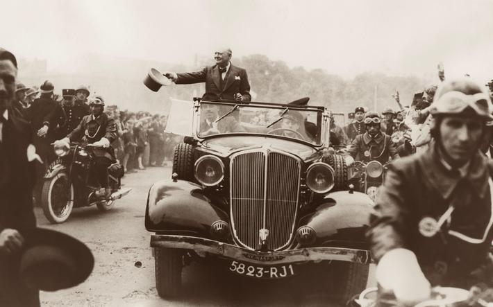 Winston Churchill waving his new gray top hat while being driven through the welcoming crowds in Met
