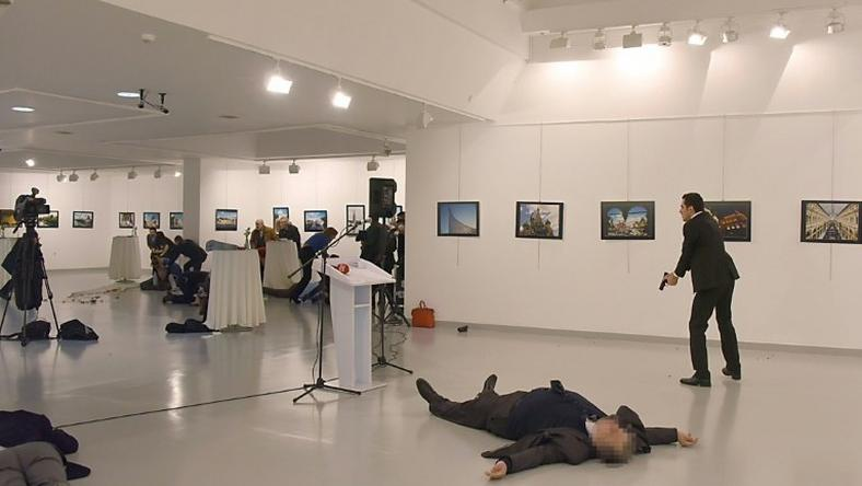 Andrei Karlov lies on the floor after being shot by Mevlut Mert Altintas (right) in Ankara on December 19, 2016