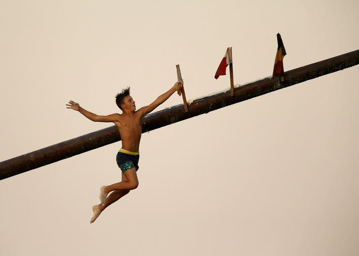 "A child competitor grabs a flag as he falls off the ""gostra"", a wooden pole covered in lard, during"