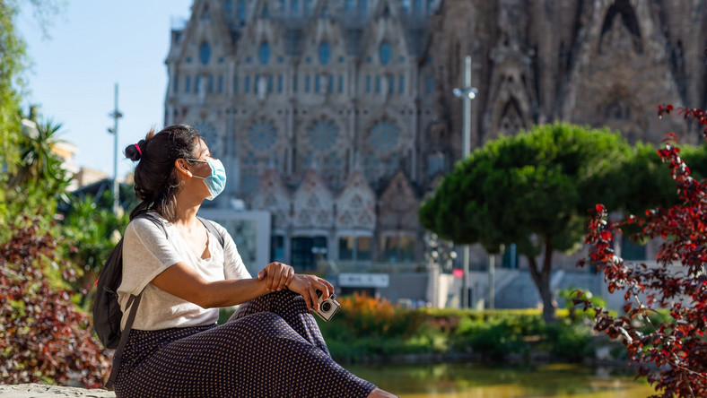 Kobieta w maseczce przy Sagrada Familia w Barcelonie