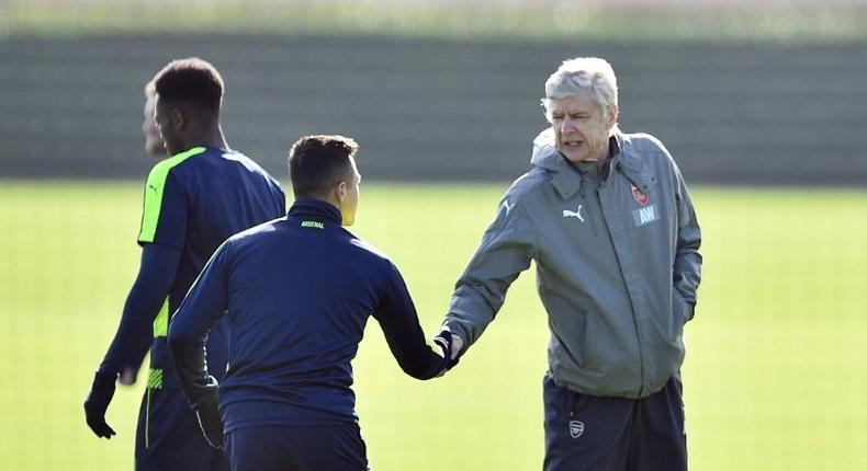 Arsenal manager Arsene Wenger (right) shakes hands with Chilean striker Alexis Sanchez during a training session in London Colney, on March 6, 2017