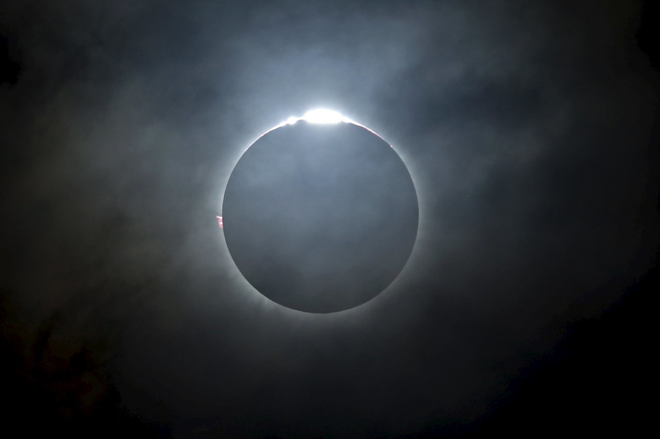 A total solar eclipse is seen from the beach on Ternate island
