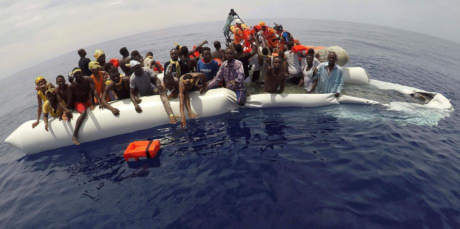 "FILE PHOTO: Migrants on a dinghy are rescued by ""Save the Children"" NGO crew from the ship Vos Hesti"