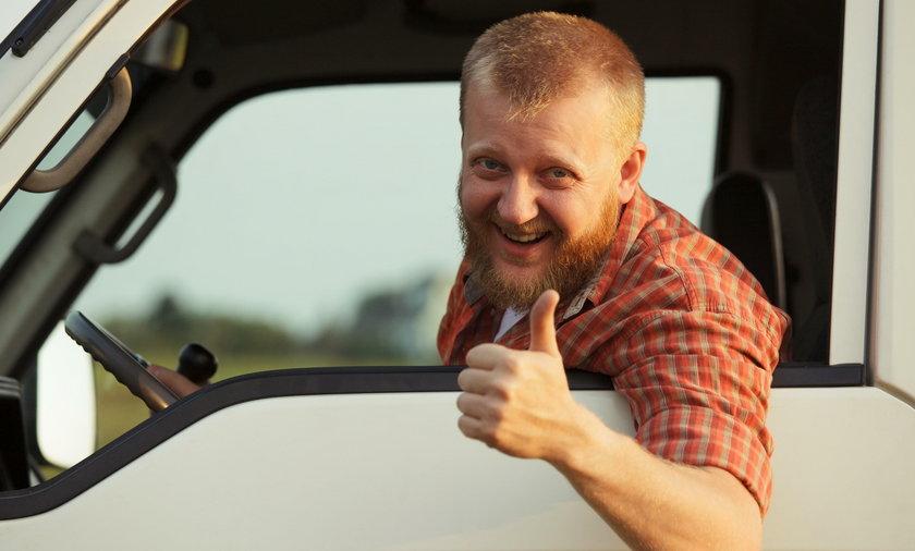 kierowca ciezarówki wyglądający z kabiny