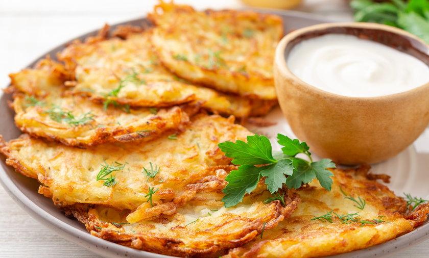 Potato pancakes or latkes or draniki with sour cream in plate on white wooden table